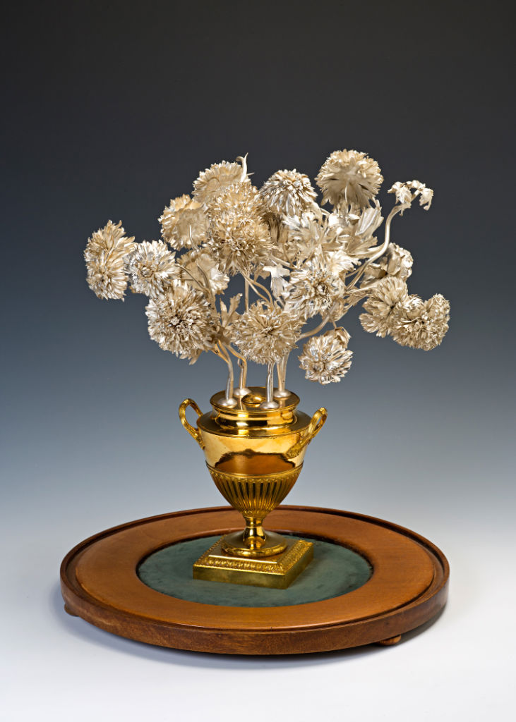 A pair of ornaments of 17th Century Italian silver flowers in 18th Century English gilt metal urns.