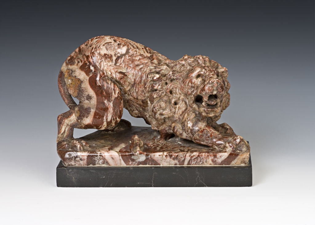 A pink marble  figure of a crouching lion, Roman, 1st/2nd  Century.