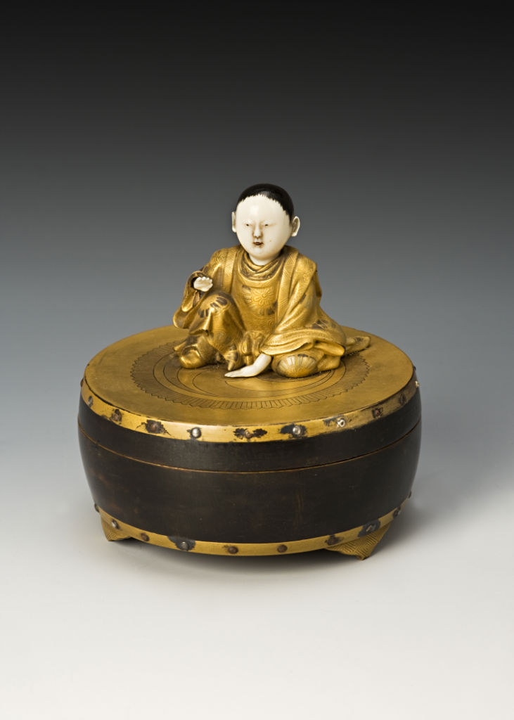 A box and cover in the form of a boy on a drum, 18th Century.