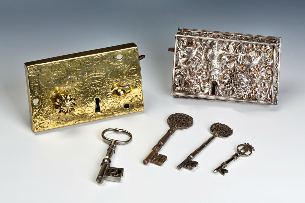 Two Ornate Door Locks, one Silver and Steel, the other Brass and Steel, English, 17th Century, together with a Group of Early Keys.