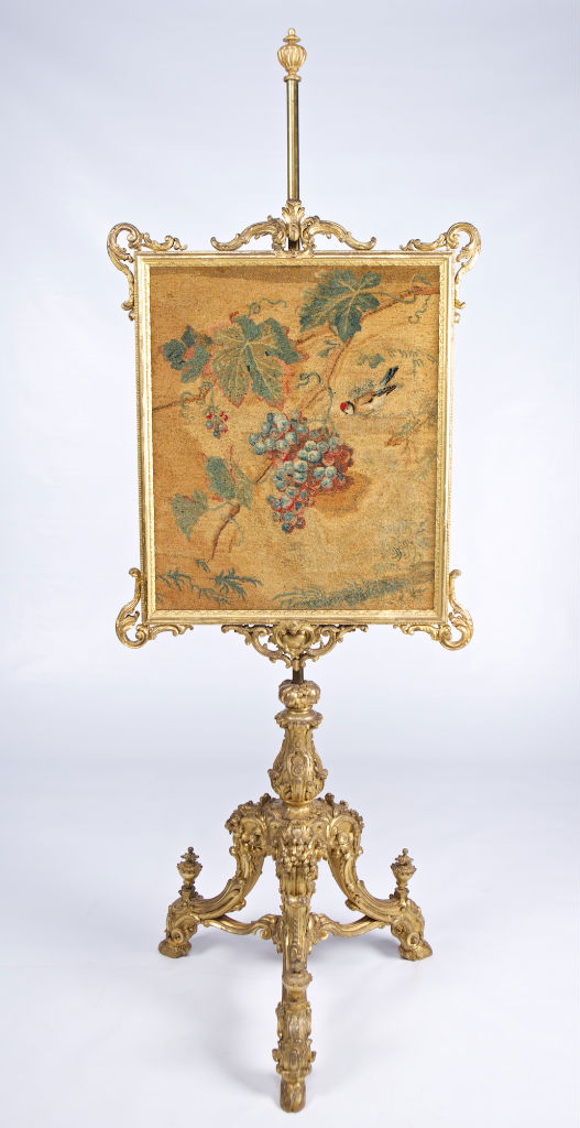A George III carved giltwood pole screen, circa 1765.