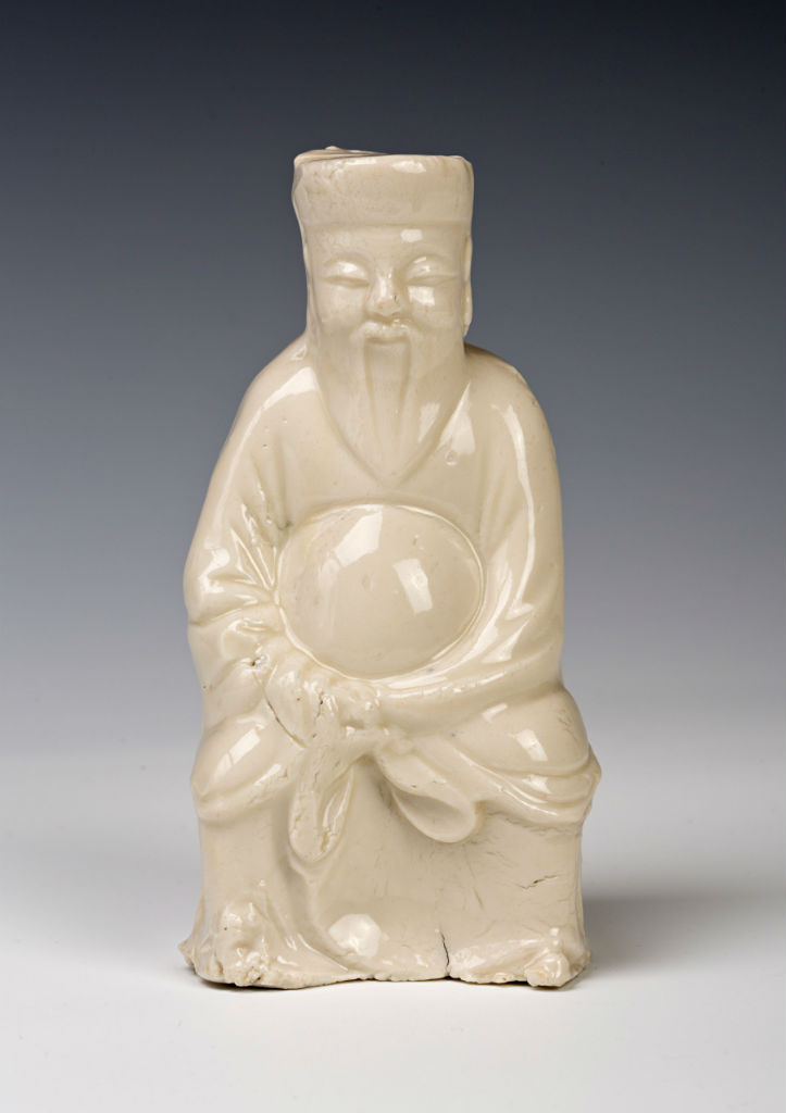 Three small Chinese blanc de chine figures of a dignitary, probably Ming (1522-1644).