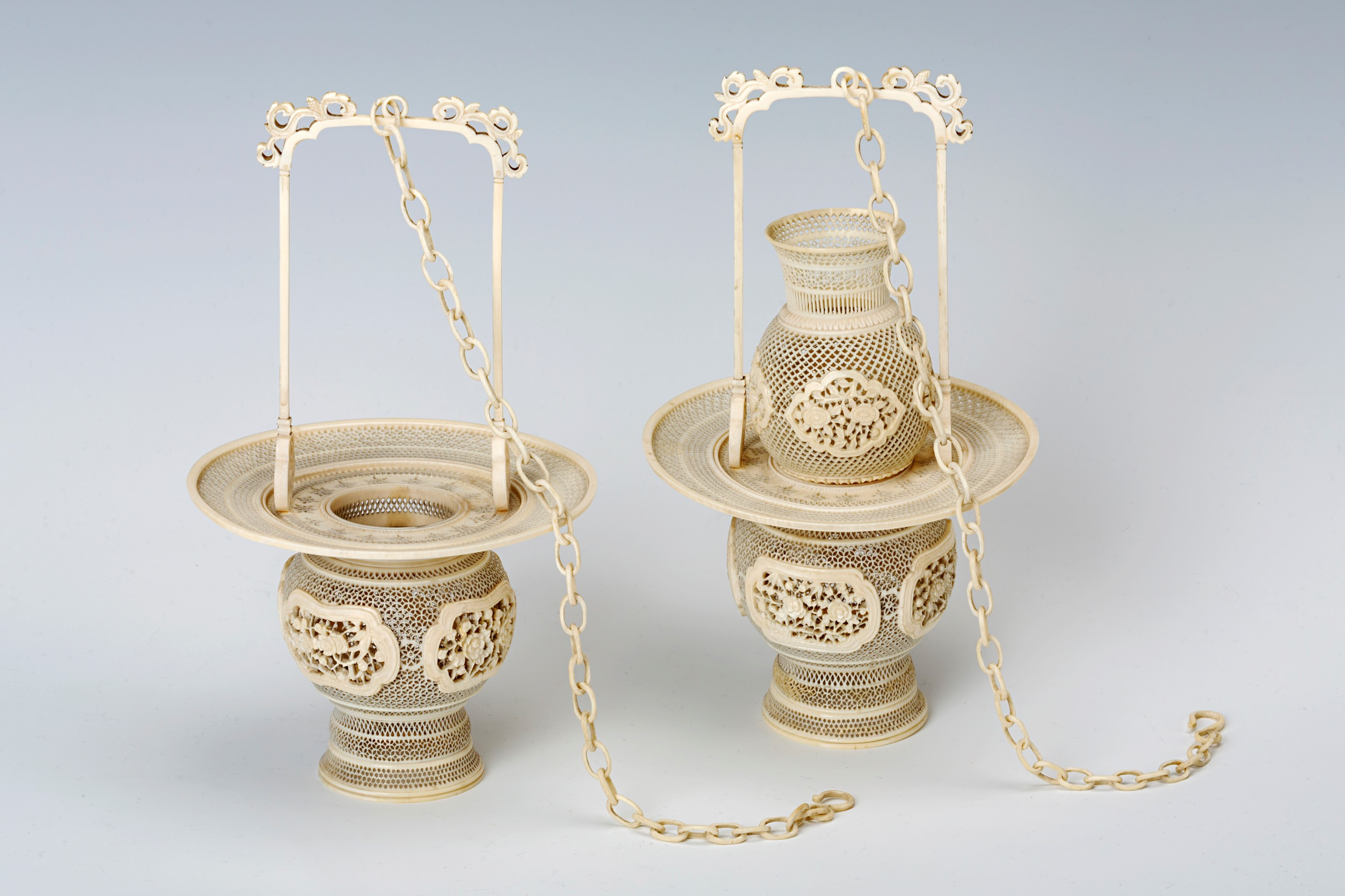 A pair of Chinese reticulated ivory hanging baskets and a pair of associated intricately carved ivory puzzle balls.